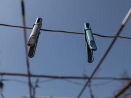 Dos pinzas para la ropa colgando de una cuerda en la calle contra un cielo azul foto