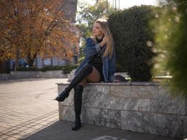Joven rubia con hermosas piernas largas con botas se sienta en la calle foto