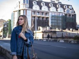 Linda adolescente rubia con cabello suelto en una chaqueta de mezclilla en el puente al aire libre foto