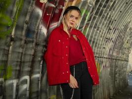 Atractiva joven hipster con gorro de punto y chaqueta roja está de pie debajo de un puente con el telón de fondo de una pared con graffiti foto
