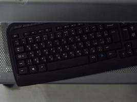 Teclado de computadora negro sobre un soporte metálico foto
