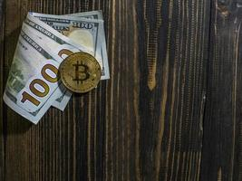 Golden Bitcoin on US dollars. Digital currency close-up on a wooden background.Real coins of bitcoin on banknotes of one hundred dollars photo