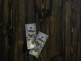 Two hundred dollars bills on a wooden background. new hundred dollar bill. Close up american dollar banknotes photo