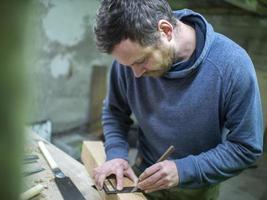 un carpintero con barba marca el cuadrado de la viga de madera foto
