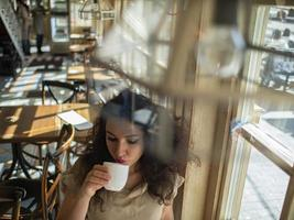 attractive girl with curly hair sits in a cafe at the table and drinks coffee photo
