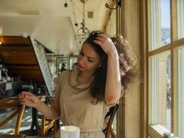 a curly-haired woman sits at a table in a cafe and straightens her hair photo