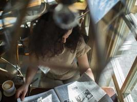 a young girl with curly hair sits at a table in a cafe and reads a newspaper photo