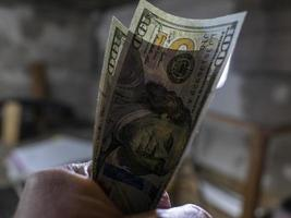 Close up of male hand holds two banknotes of hundred dollars. new hundred-dollar bills.Money USA dollar banknotes photo