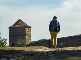 Un hombre con un suéter con capucha y un gorro de punto está caminando por el camino hacia la fortaleza con el telón de fondo de la torre y el cielo azul foto