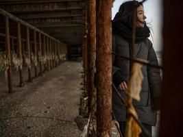 young girl in a coat stands near metal rusty structures near the sea coast photo