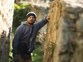 bearded man in knitted hat and jacket with hood posing in a ravine of a fortress photo