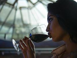 portrait of an attractive girl with beautiful lips who drinks red wine from a glass photo