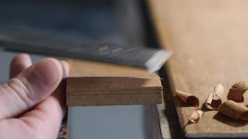 chisel work. craftsman carpenter removes excrd with aess thickness from a wooden boa flat chisel. video