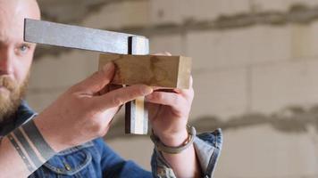 le charpentier vérifie l'angle de 90 degrés avec l'équerre d'essai video