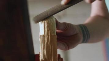 a joiner processes a piece of wood with a file. video