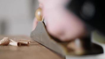 charpentier rabote une petite planche de bois avec un rabot à main. video
