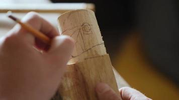 wood carver draws a sketch of a robot head on a piece of wood video