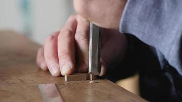 carpenter cuts off the excess wood product with a flat chisel. video