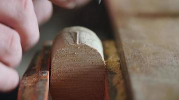 a woodcarver carves a poplar product using a knife video