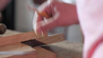 un charpentier marque une planche de bois avec un carré d'essai video