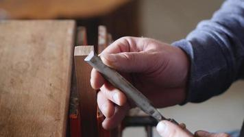 A carpenter removes chamfer from a piece of wood with a chisel. video