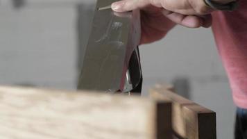 un travailleur masculin lubrifie la lame d'un avion à main avec de l'huile. video