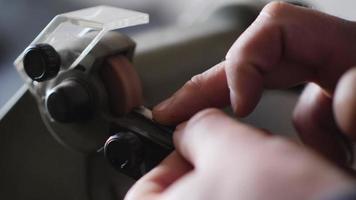 un ouvrier affûte un ciseau à partir d'un roulement sur une meule électrique. video