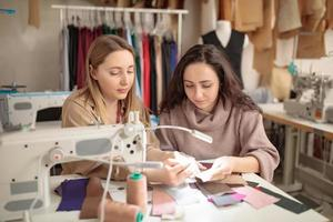 Designers inspecting sample fabric with their hands in a studio photo