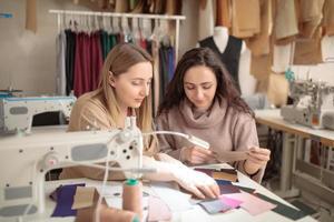 Cerca de la estilista de moda femenina y el cliente sosteniendo muestras de color de telas eligiendo el diseño para el nuevo vestido, espacio de copia foto