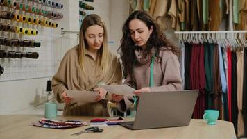 Hermosas mujeres jóvenes sastres eligiendo forro de tela para prendas de vestir del catálogo cerca de la computadora portátil foto