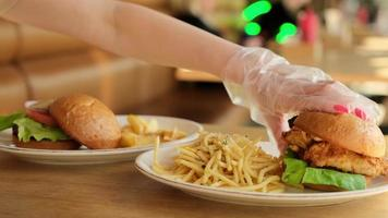 Woman in gloves taking hamburger for eating photo