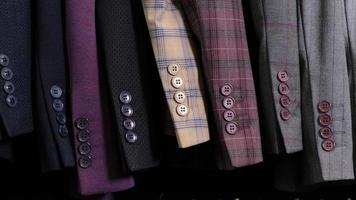 Menswear classical different suits in row in clothing shop in mall. View of a row of jackets sleeves with buttons. photo