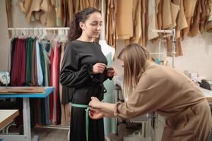 sastre femenino mide el tamaño de las caderas del cliente foto