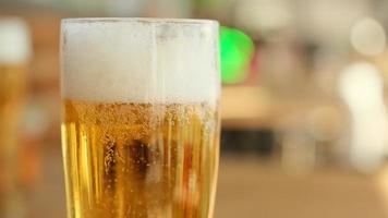 vaso de cerveza de cerca con espuma en cámara lenta foto