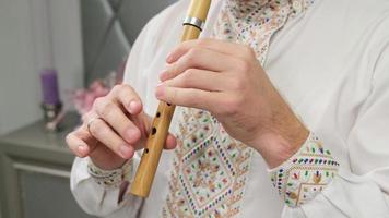 A man playing woodwind wooden flute recorder photo