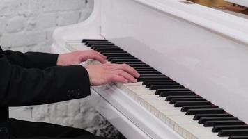una foto de manos masculinas tocando el piano de cola blanco brillante