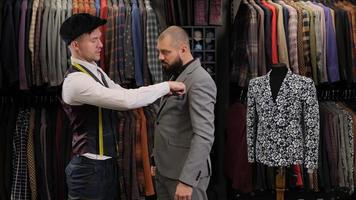 The male tailor designer measuring the suit with a measuring tape on male model photo