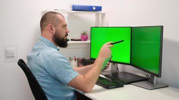 guapo fotógrafo independiente hombre mirando a dos monitores y un teléfono inteligente con pantallas verdes. foto
