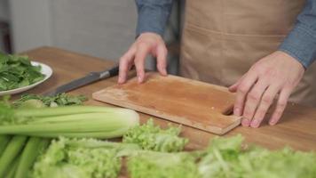 Primer plano de manos de hombre cortando verduras en tabla de cortar de madera para ensalada en la mesa con comida sana en la cocina. foto