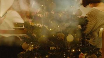 Christmas tree with balls and flashing lights on background holiday table. view through the window photo
