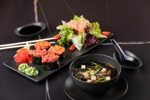 Japanese food, sushi, rolls, soup, salad on black background photo