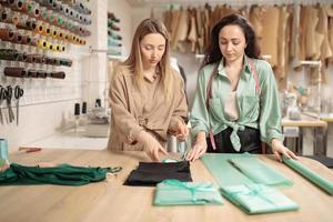 Two Young fashion designers or tailors in packing new clothes in before delivering in workshop studio photo
