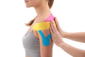 Fisioterapeuta poniendo kinesio tape en el hombro de las pacientes aisladas sobre fondo blanco. foto