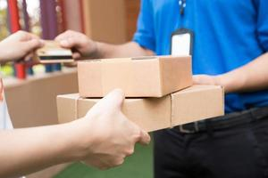 Customer paying by credit card for shipping product and sending to shipping man photo