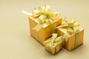 Christmas gold gift box on brown background photo