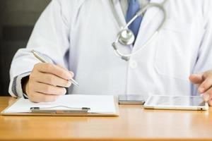 Professional doctor writing note for medical records about new patient photo
