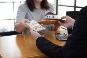 Women holding contract and document about home mortgage submit to bank and received money photo
