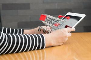 Woman hand holding tablet and shopping cart photo