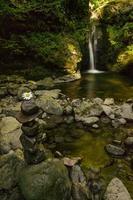 Piedras apiladas y flores en frente de una cascada en las montañas de los Cárpatos que fluye de un barranco tallado en piedra y cubierto de musgo foto