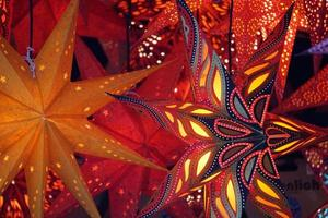 Lights In Darkness. Red And Gold Traditional Stars As Christmas Lanterns On The Market. photo